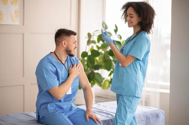 그녀의 동료를 위해 예방 접종을 준비하는 여성 의사