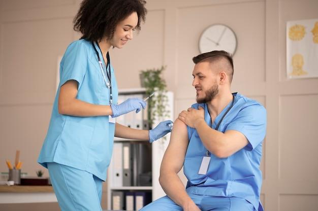 Женщина-врач готовит вакцинацию для своего коллеги
