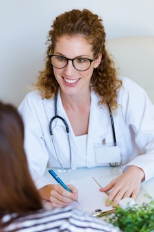 Female doctor prescribing medication for patient in the office.