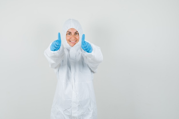 Medico femminile in tuta protettiva, guanti che mostrano i doppi pollici in su e che sembrano felici