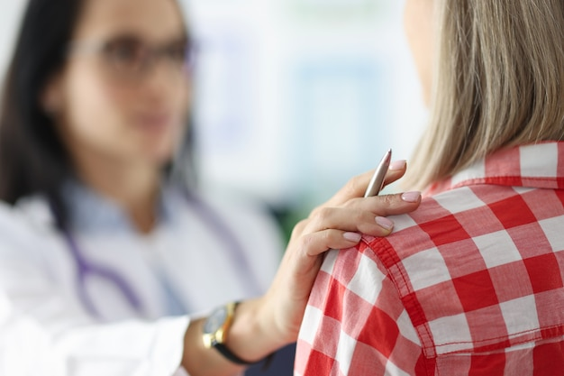 Female doctor put hand sympathetically on the patient shoulder patient support during the