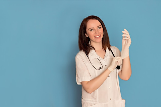 Female doctor puts on medical gloves, stethoscope on a blue background. copy space