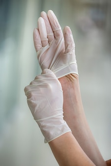 여성 의사는 병원에서 열심히 일하기 전에 보호 수술 장갑을 착용