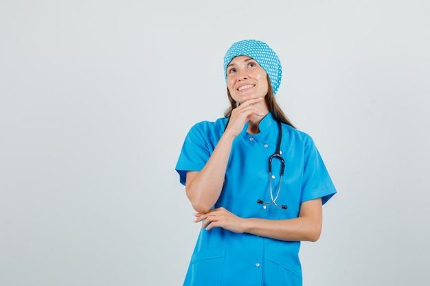 Female doctor putting hand while propping up on chin in blue uniform and looking cheerful. front view.