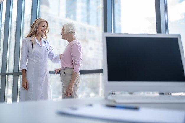 患者の肩に手を置く女性医師