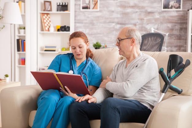 요양원에서 노인에게 책을 읽는 여성 의사.