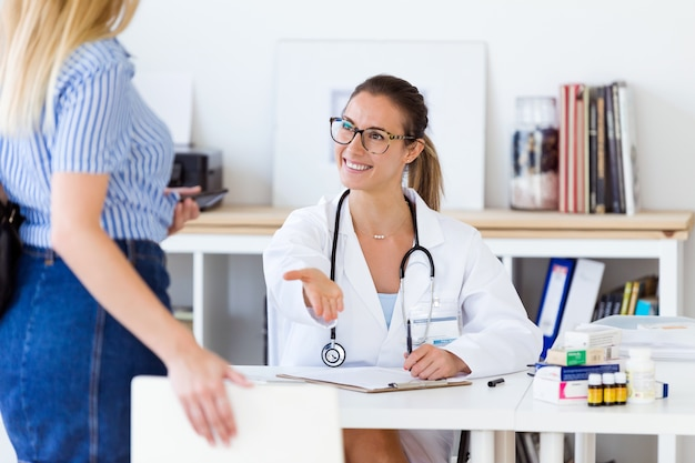 Female doctor receiving her patient in the office.