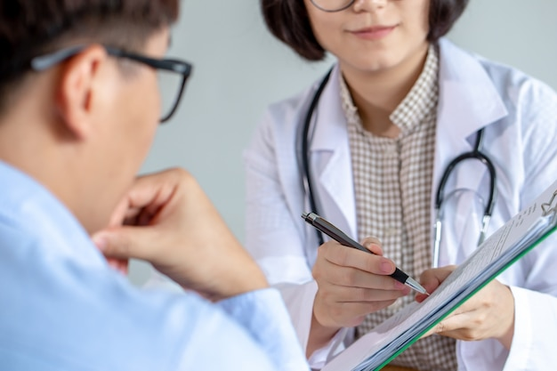 Female doctor report treatment results to patient.