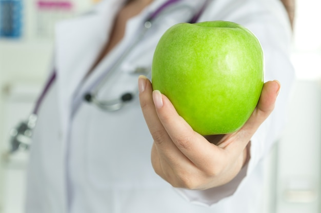 Female doctor's hand giving fresh green apple. healthy life, wholesome and healthcare concept.