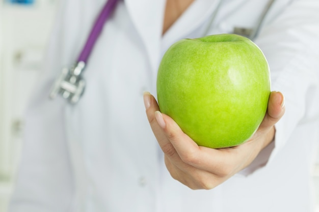 Female doctor's hand offering fresh green apple. healthy life, wholesome and healthcare concept.