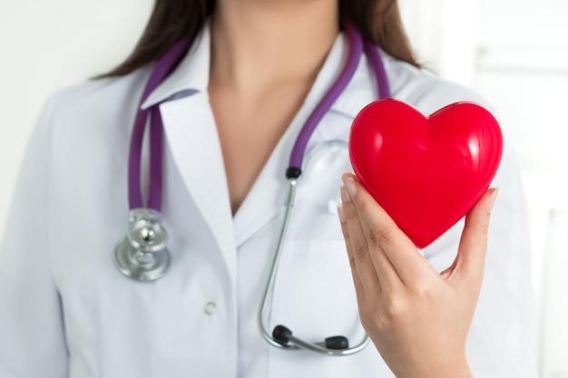 女医の手が胸の前で赤いハートを保持しています。医師の手のクローズアップ。医療支援、予防または保険のコンセプト。