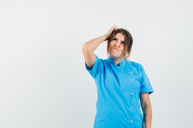 Dottoressa che si gratta la testa in uniforme blu e sembra sognante