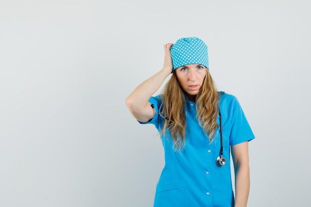 女医が青い制服を着た頭を悩まと物思いにふける。