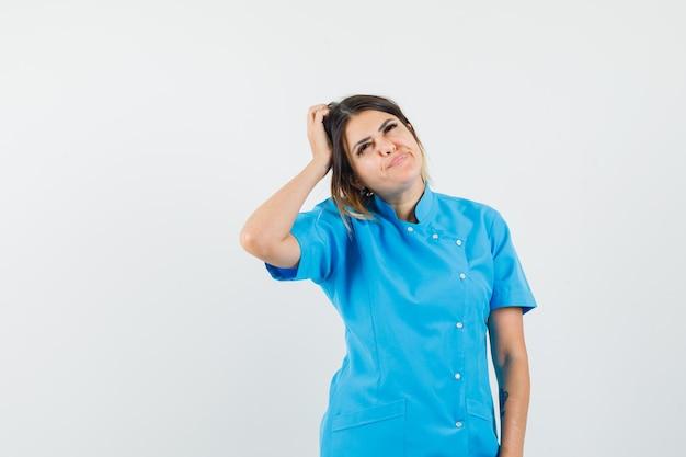 青い制服を着て見上げて思慮深く見ながら頭を掻く女医