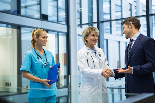 Female doctor shaking hands with businessman