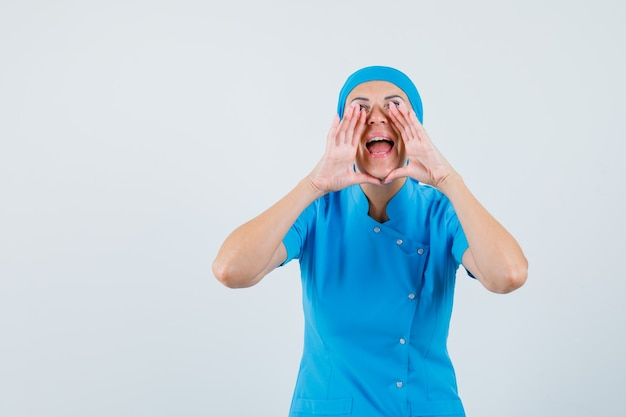 Female doctor shouting or announcing something in blue uniform and looking happy. front view.