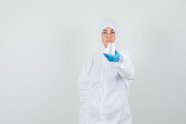 Medico femminile che mostra una bottiglia di pillole in tuta protettiva, guanti e aspetto serio