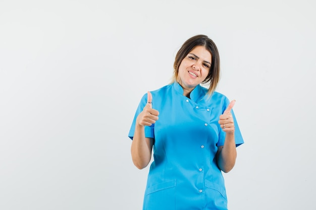 青い制服を着て二重の親指を見せて陽気に見える女性医師
