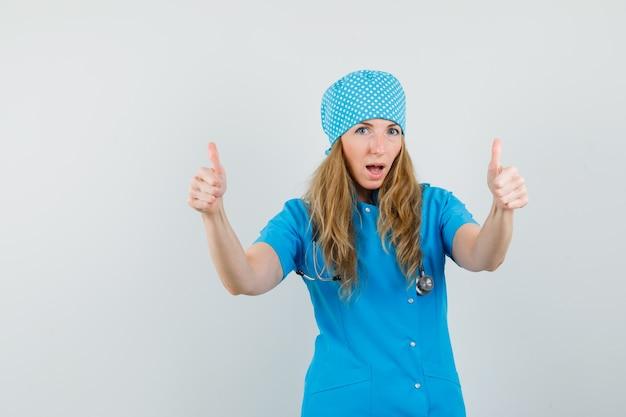 Женщина-врач показывает двойные пальцы вверх в синей форме