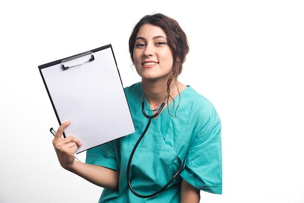 Medico femminile che mostra appunti vuoti con penna e stetoscopio su sfondo bianco. foto di alta qualità