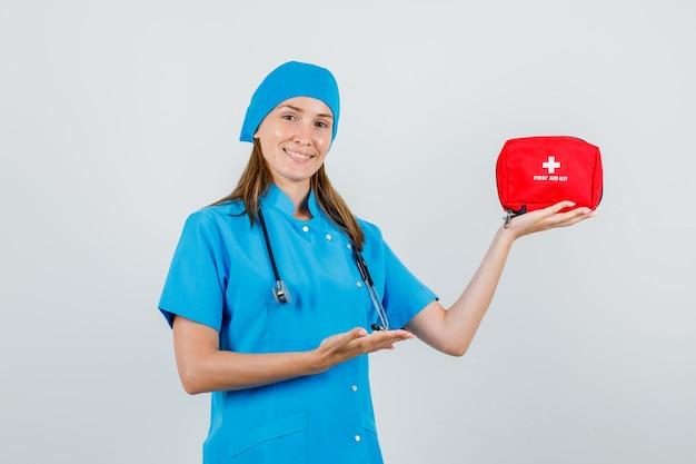 Женщина-врач показывает аптечку в форме и выглядит весело. передний план.