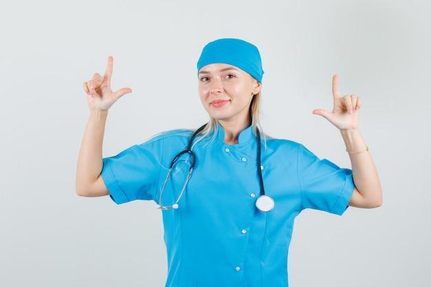 銃のジェスチャーを示し、青い制服を着て笑っている女性医師