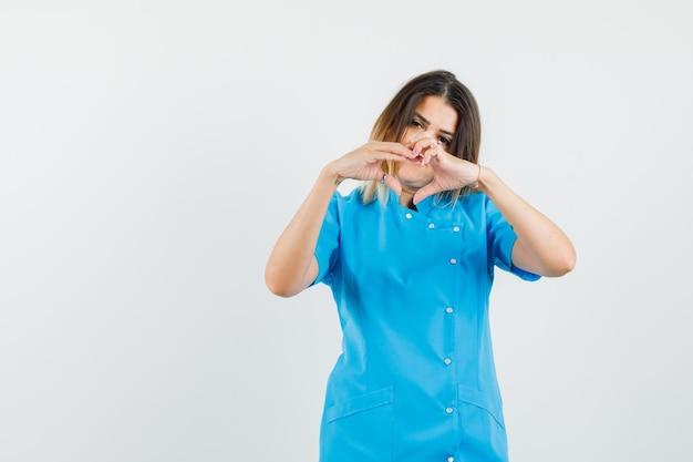 Женщина-врач показывает жест сердца в синей форме и выглядит весело