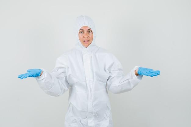 Medico femminile che mostra gesto impotente in tuta protettiva, guanti e sguardo confuso