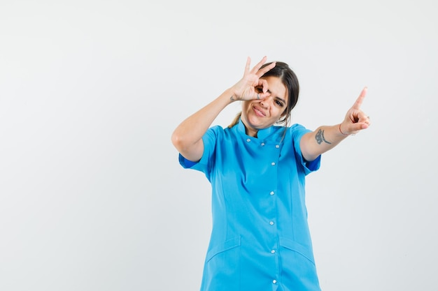 Female doctor showing hold on a minute and ok gesture in blue uniform