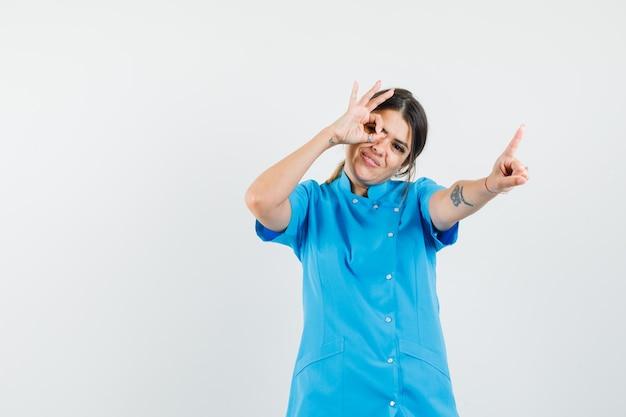 青い制服を着た女性医師が1分とokのジェスチャーを保持していることを示しています