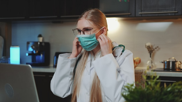 Female doctor showing how to wear medical mask by video call on computer