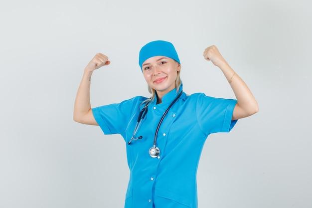 筋肉を見せ、青い制服を着て微笑んで、強く見える女医。