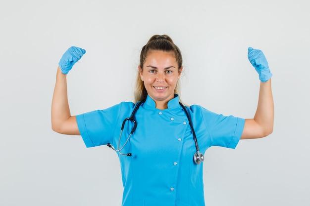 青い制服を着た筋肉を示す女医