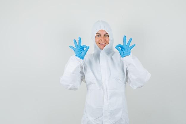 Medico femminile che mostra gesto giusto in tuta protettiva