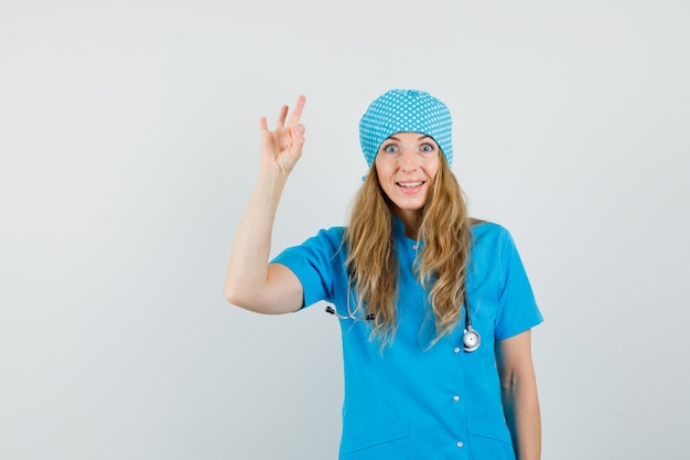 Female doctor showing ok sign in blue uniform and looking merry