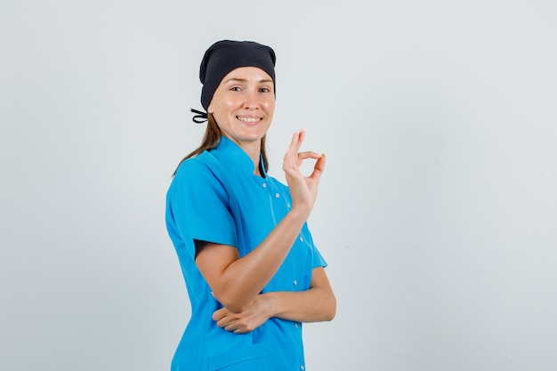 青い制服、黒い帽子でokサインを示し、陽気に見える女性医師。正面図。