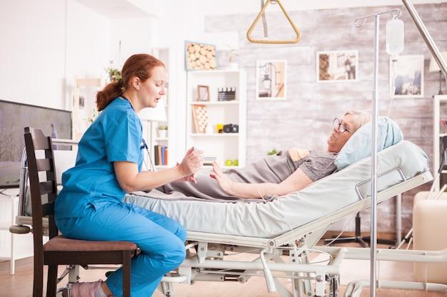 요양원에서 늙은 여자에게 그녀의 약을 보여주는 여성 의사.
