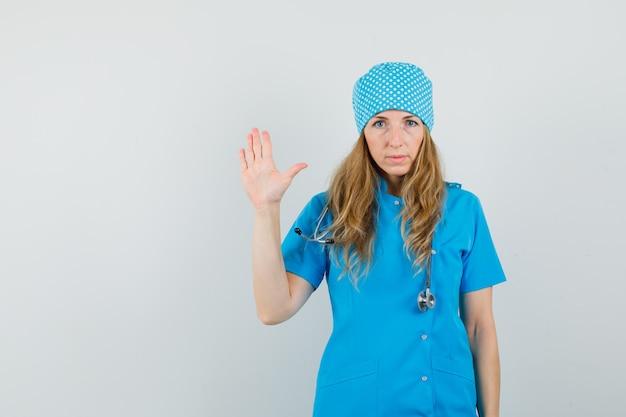 Женщина-врач показывает ладонь и смотрит в камеру в синей форме