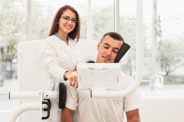 Female doctor showing patient how to use medical machine