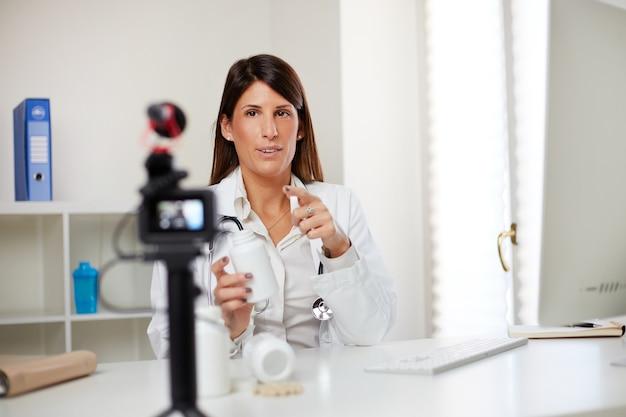 ピルを見せてビデオvlogを記録する女性医師