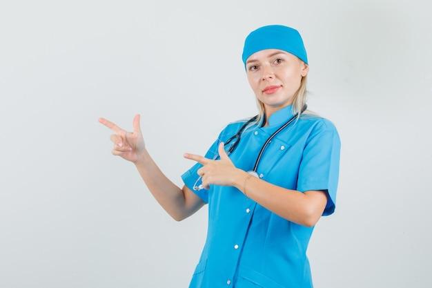 ピストルジェスチャーを示し、青い制服を着て笑っている女性医師