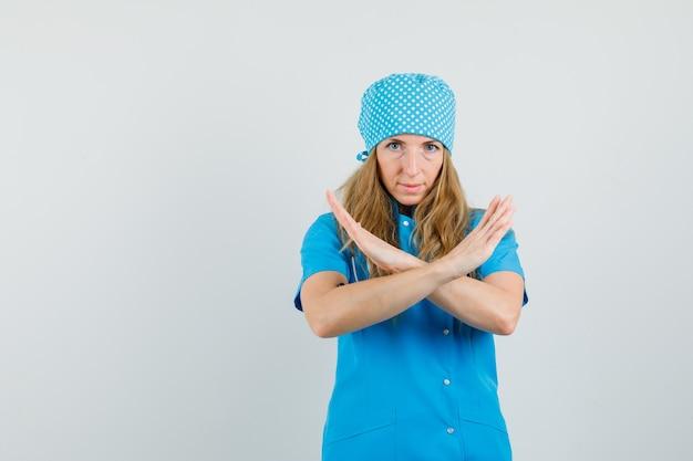 Женщина-врач показывает жест отказа в синей форме и выглядит серьезно