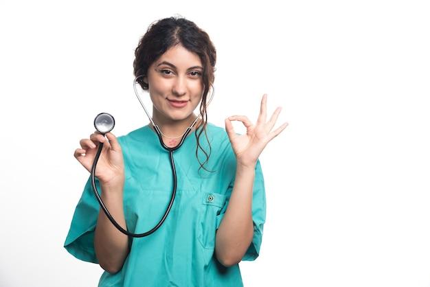 白い背景にokジェスチャーで聴診器を示す女性医師