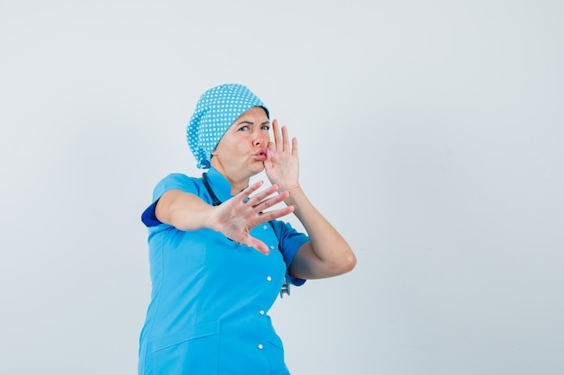 Female doctor showing stop gesture with mouth shut as zip in blue uniform and looking scared , front view.