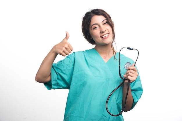 Medico femminile che mostra i pollici in su su priorità bassa bianca. foto di alta qualità