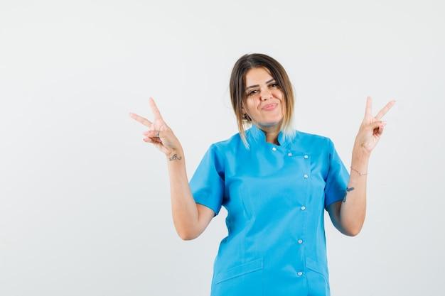 파란색 유니폼에 v 기호를 보여주는 여성 의사와 행복을 찾고
