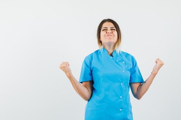 Medico donna che mostra il gesto del vincitore in uniforme blu e sembra felice