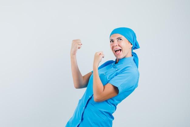 Женщина-врач показывает жест победителя в синей форме и выглядит счастливым, вид спереди.