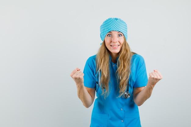 Женский доктор показывает жест победителя в синей форме и выглядит счастливым.