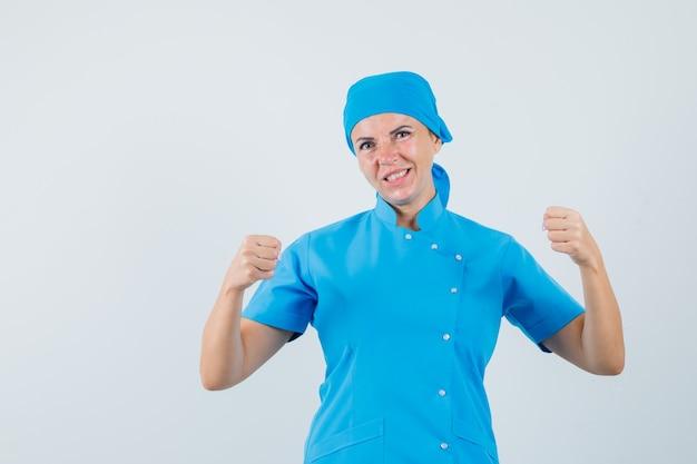 青い制服を着て勝者のジェスチャーを示し、幸運な、正面図を探している女性医師。